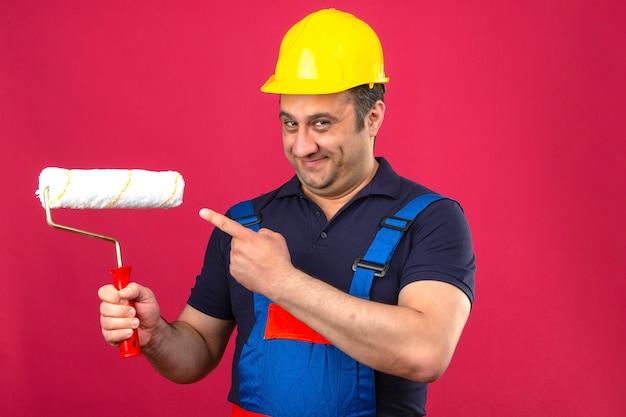 Человек-строитель в строительной форме и защитном шлеме стоит с малярным валиком, улыбаясь и указывая пальцем, чтобы нарисовать валик над изолированной розовой стеной