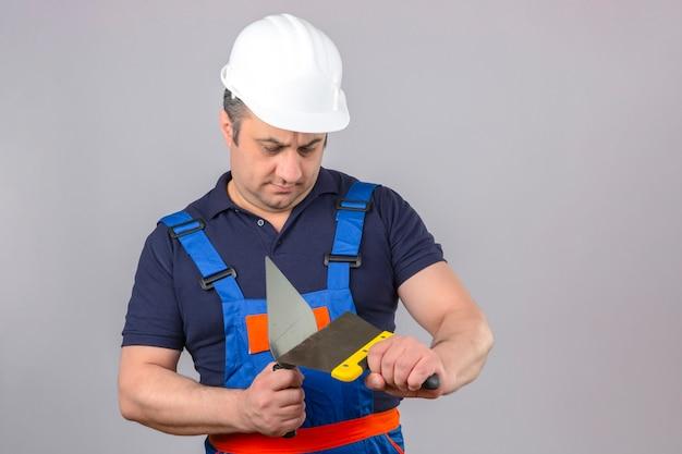 Мужчина-строитель в строительной форме и защитном шлеме стоит с шпателем и шпателем в руках с серьезным лицом над изолированной белой стеной