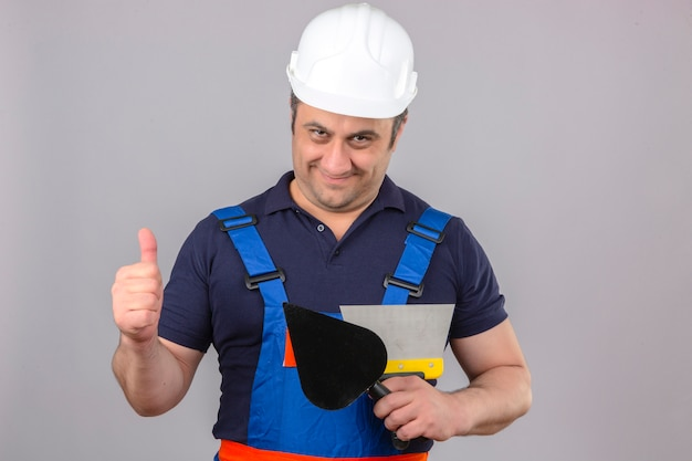 Человек-строитель в строительной форме и защитном шлеме, стоящий со шпателем и шпателем, показывает палец вверх со счастливым лицом и улыбается над изолированной белой стеной