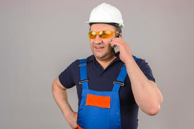 孤立した白い壁に笑みを浮かべて携帯電話で話している建設の制服と安全ヘルメットを身に着けているビルダー男