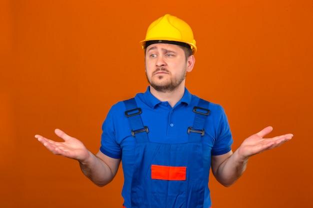 ビルダーの男が身に着けている建設のユニフォームとセキュリティヘルメット無知と混乱した式腕と手で孤立したオレンジ色の壁に疑問の概念を発生