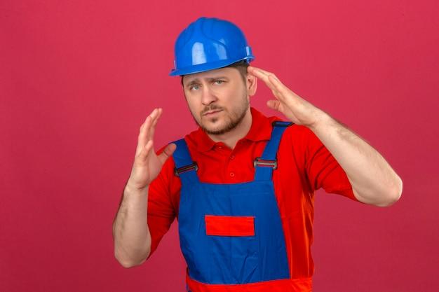 ビルダーの男が身に着けている建設の制服とセキュリティヘルメット不機嫌と孤立したピンクの壁に発生した手で恐ろしい立っています。