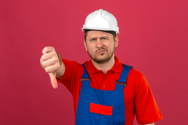 Человек-строитель в строительной форме и защитном шлеме недоволен, показывая большой палец вниз, стоя над изолированной розовой стеной
