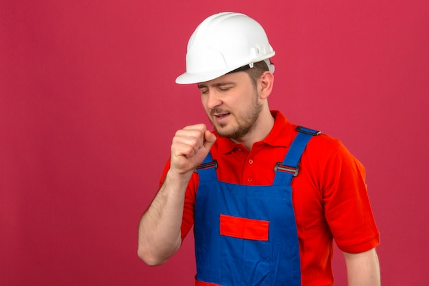 Человек-строитель в строительной форме и защитном шлеме чувствует себя плохо и кашляет, стоя над изолированной розовой стеной