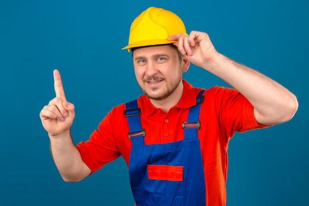 건설 유니폼 및 보안 헬멧을 착용하는 작성기 남자는 고립 된 파란색 벽 위에 서있는 그의 헬멧을 만지고 손가락을 가리키는 아이디어를 얻었습니다.