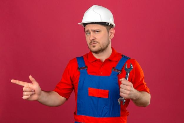 孤立したピンクの壁の上に自信を持って立っているを見て側に指で指しているレンチを保持している建設の制服とセキュリティヘルメットを身に着けているビルダー男