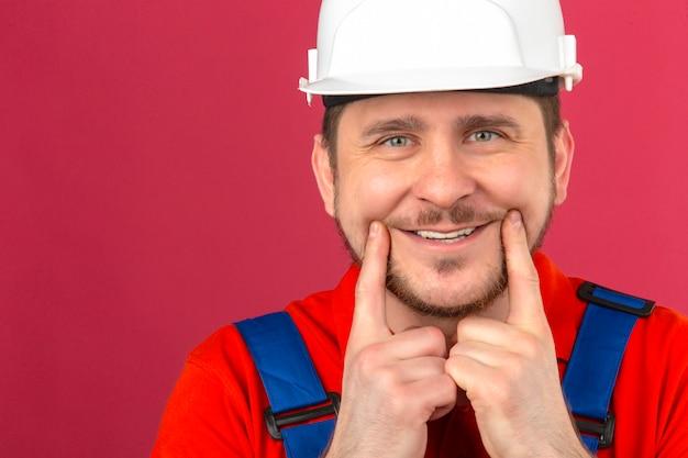 Мужчина-строитель в строительной форме и защитном шлеме держит пальцы на щеках и пытается заставить себя улыбнуться над изолированной розовой стеной