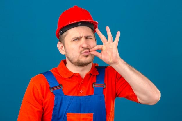 Человек-строитель в строительной форме и защитном шлеме делает жест молчания, словно закрывает рот на молнии над изолированной синей стеной