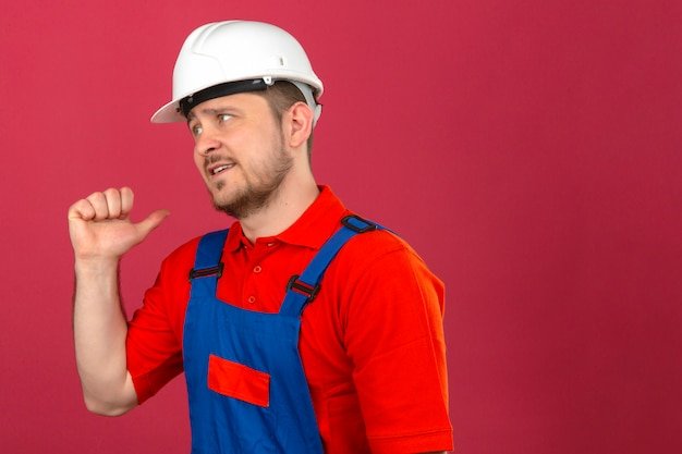 建設の制服とセキュリティヘルメットを身に着けているビルダーの男の後ろで後ろを指して手と親指を分離した暗いピンクの壁の上に立って不機嫌