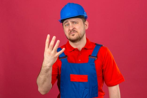 Человек-строитель в строительной форме и защитном шлеме показывает и указывает пальцами номер четыре со скептическим выражением лица над изолированной розовой стеной