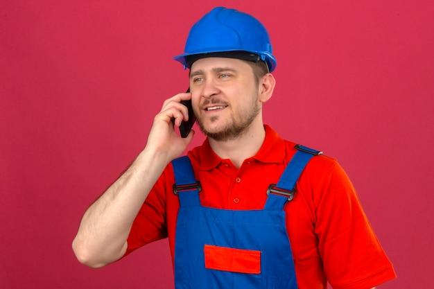 Человек-строитель в строительной форме и шлеме безопасности разговаривает по мобильному телефону, уверенно смотрит на изолированную розовую стену