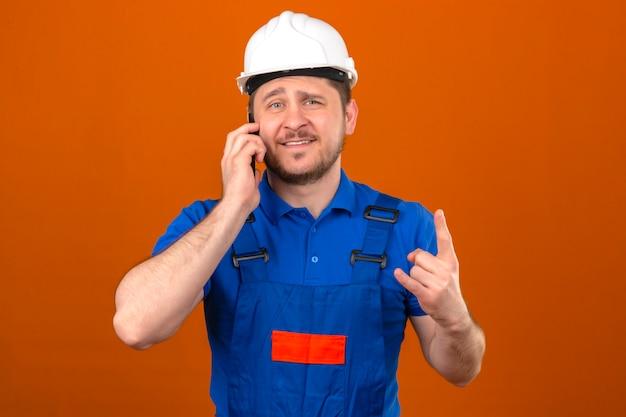 孤立したオレンジ色の壁に陽気に立っている笑顔のロックシンボルを示す携帯電話で話している建設の制服とセキュリティヘルメットを身に着けているビルダー男