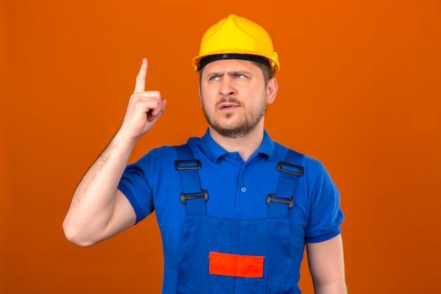 建設の制服とセキュリティヘルメットを身に着けているビルダー男は、孤立したオレンジ色の壁の上に立っている指で警告サインを示す彼の指を持ち上げる危険を警告します