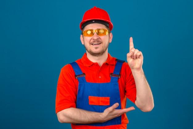 Vetri d'uso dell'uniforme della costruzione dell'uomo del costruttore e casco di sicurezza che indicano con il dito su che sembra nuovo concetto sorridente sicuro di idea sopra la parete blu isolata