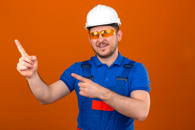 Builder man wearing construction uniform glasses and security helmet smiling cheerfully and pointing with hands and finger to the side standing over isolated orange wall
