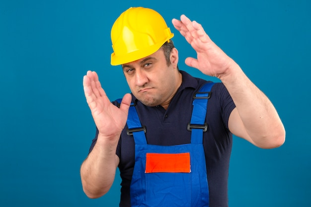 Builder man wearing construction uniform and safety helmet gesturing with hands showing size sign measure symbol over isolated blue wall