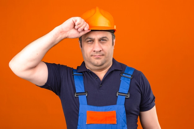 Builder man wearing construction uniform and safety helmet holding his helmet like salute with serious face over isolated orange wall