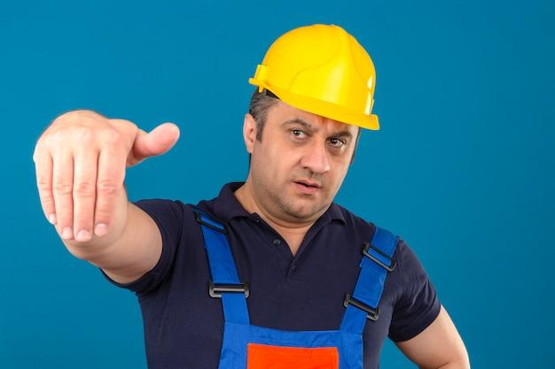L'uniforme di costruzione d'uso dell'uomo del costruttore e la fabbricazione del casco di sicurezza vengono qui gesto con la mano con il fronte serio sopra la parete blu isolata