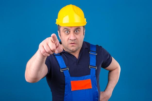 Uomo del costruttore che indossa l'uniforme di costruzione e il casco di sicurezza che punta scontento e frustrato per la fotocamera arrabbiato e furioso con te sul muro blu isolato