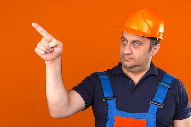 Builder man wearing construction uniform and safety helmet pointing to the side standing with serious face over isolated orange wall