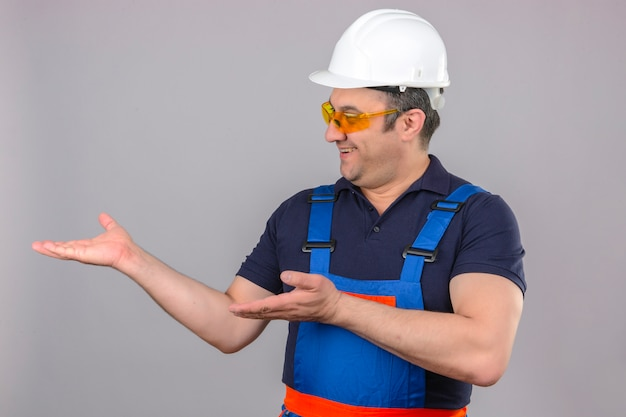 Builder man wearing construction uniform and safety helmet pointing to the side with hands and open palms presenting ad smiling happy and confident over isolated white wall