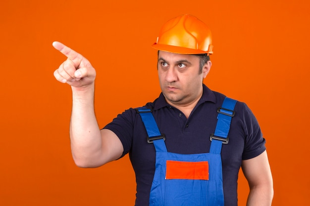 Builder man wearing construction uniform and safety helmet pointing to the side with serious face looking displeased over isolated orange wall
