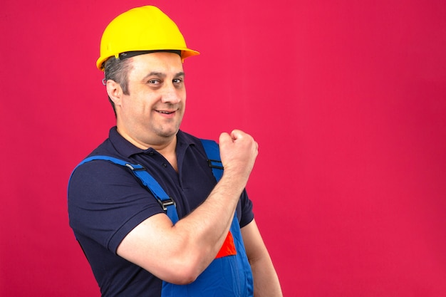 Builder man wearing construction uniform and safety helmet showing biceps smiling with happy face winner concept standing over isolated pink wall