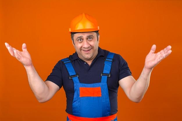 Uomo del costruttore che indossa l'uniforme di costruzione e il casco di sicurezza che scrolla le spalle allargando le mani non capendo cosa è successo espressione confusa e confusa sopra l'arancia isolata