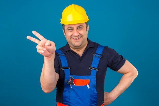 Builder man wearing construction uniform and safety helmet smiling pointing with fingers to the side over isolated blue wall