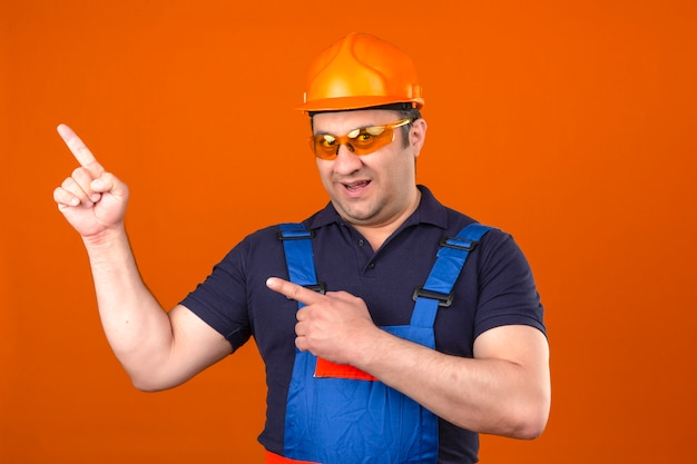 Builder man wearing construction uniform and safety helmet smiling with happy face and pointing to the side with fingers over isolated orange wall