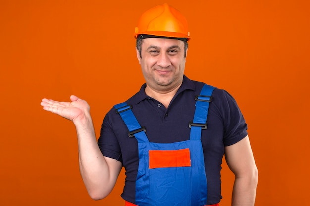 Builder man wearing construction uniform and safety helmet smiling with happy face presenting and pointing with palm of hand over isolated orange wall