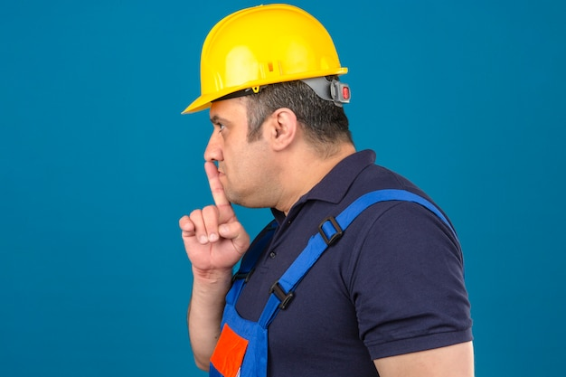 Builder man wearing construction uniform and safety helmet standing sideways making hush sign over isolated blue wall
