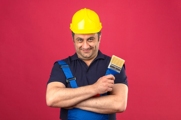 Builder man wearing construction uniform and safety helmet standing with crossed arms holding paint brush smiling with happy face over isolated pink wall