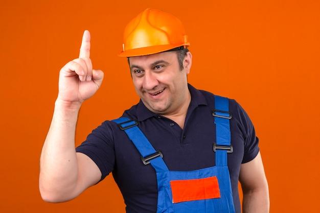 Uniforme d'uso della costruzione dell'uomo e casco di sicurezza del costruttore che stanno con il fronte felice e dito sorridente indicante sul nuovo concetto di idea sopra la parete arancio isolata
