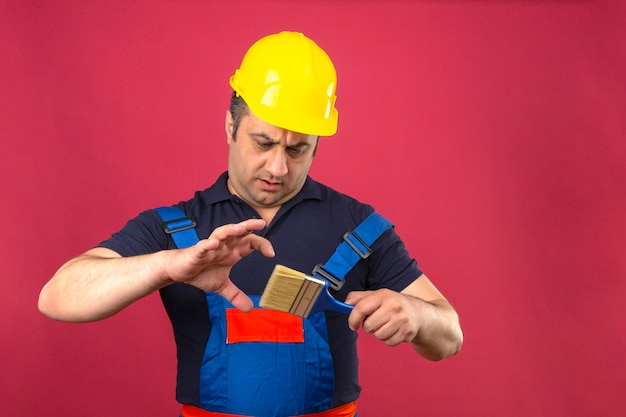 Builder man wearing construction uniform and safety helmet standing with paint brush and looking at it with serious face over isolated pink wall