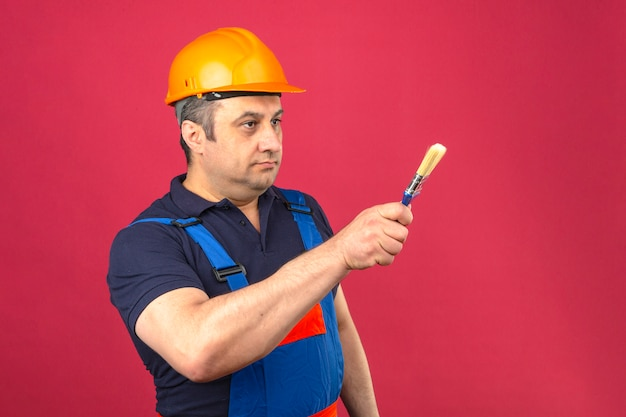 Builder man wearing construction uniform and safety helmet standing with paint brush and pointing with it to the side over isolated pink wall