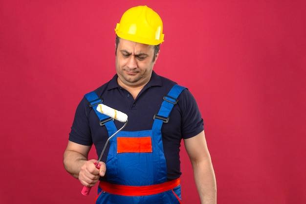 Builder man wearing construction uniform and safety helmet standing with paint roller feeling skeptic doubtful over isolated pink wall
