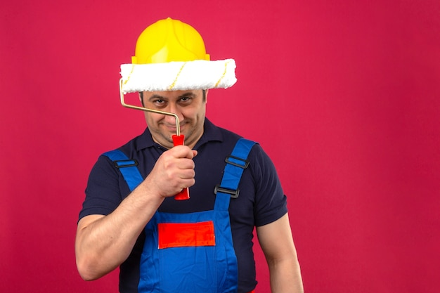 Uniforme d'uso della costruzione dell'uomo e casco di sicurezza del costruttore che stanno con il rullo di pittura che sorride sleale sopra isolato sopra la parete rosa isolata