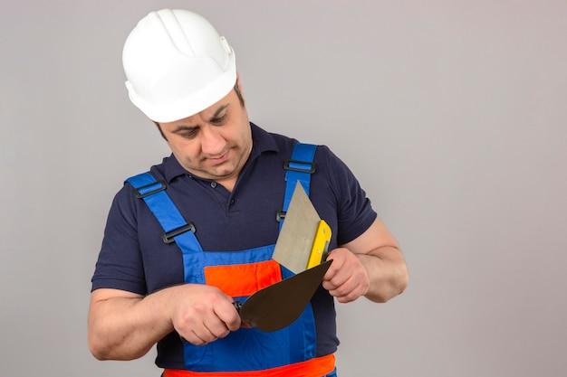 Uniforme da costruzione e casco di sicurezza d'uso dell'uomo del costruttore che stanno con il coltello e la cazzuola di mastice in mani con il fronte serio sopra la parete bianca isolata