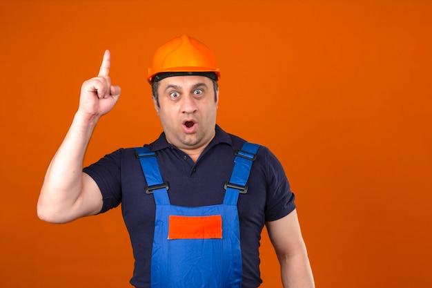 Uniforme d'uso della costruzione dell'uomo e casco di sicurezza del costruttore che stanno con il fronte sorpreso che indica dito sul nuovo concetto di idea sopra la parete arancio isolata