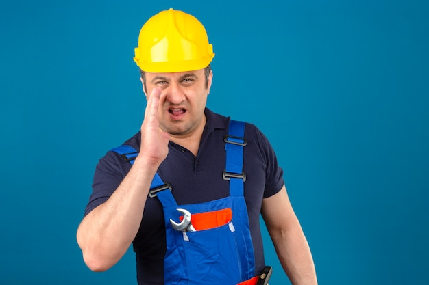 Builder man wearing construction uniform and safety helmet yelling something and keeping hand near his opened mouth over isolated blue wall