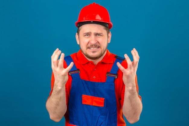 L'uomo del costruttore che indossa l'uniforme della costruzione e il casco di sicurezza pazza e pazza sta con l'espressione aggressiva e le armi alzate sopra la parete blu isolata