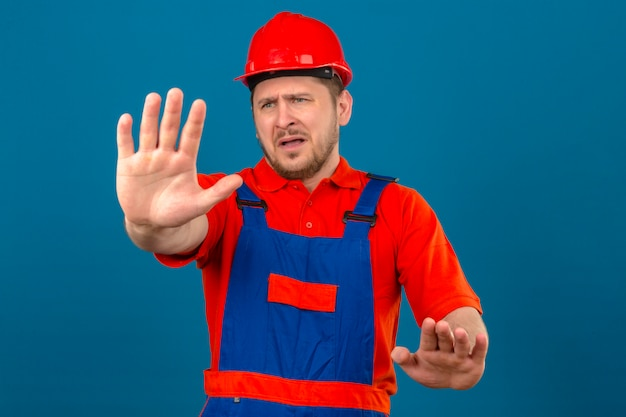 Builder man wearing construction uniform and security helmet displeased and fearful making stop sign with hands standing over isolated blue wall