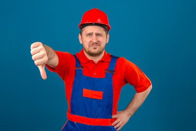 Uniforme di costruzione da portare dell'uomo del costruttore e casco di sicurezza dispiaciuto mostrando pollice giù che controlla parete blu isolata