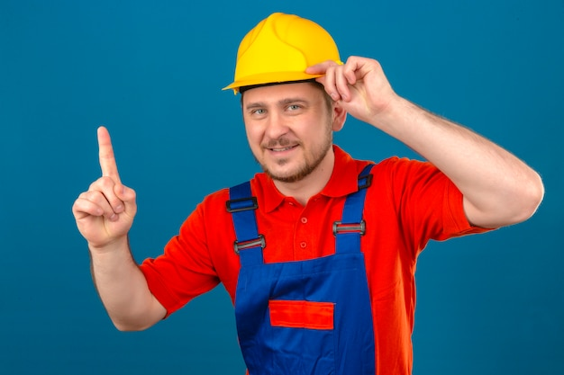Builder man wearing construction uniform and security helmet got an idea pointing finger up touching his helmet standing over isolated blue wall