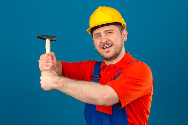 Uniforme edile da portare dell'uomo del costruttore e casco di sicurezza che tengono martello in mani che sorridono allegramente controllando parete blu isolata