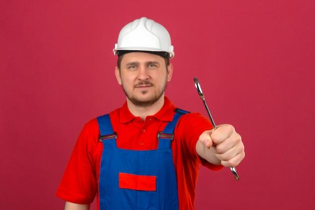 Uniforme da costruzione dell'uomo del costruttore e chiave di tenuta del casco di sicurezza a disposizione che sembrano sicuri sopra la parete rosa isolata