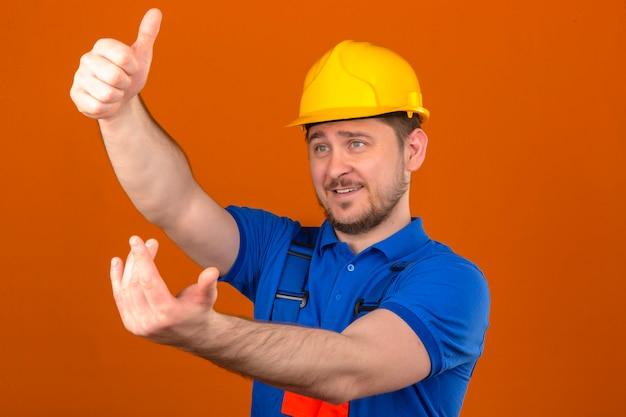 Uniforme edile da portare dell'uomo del costruttore e casco di sicurezza che invitano ad avvicinarsi facendo un gesto con la mano che è positiva e amichevole sopra la parete arancione isolata