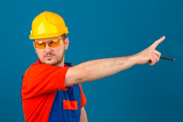 Builder man wearing construction uniform and security helmet looking aside pointing with finger ti another side with angry expression on face over isolated blue wall