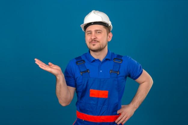 Uniforme da costruzione e casco di sicurezza d'uso dell'uomo del costruttore che indicano da parte con la palma aperta della mano che mostra sorridere dello spazio della copia sicuro sopra la parete blu isolata
